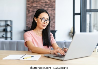 Beautiful and clever young asian girl wearing stylish eyeglasses is using a laptop in cozy apartment, e-studying, working remotely