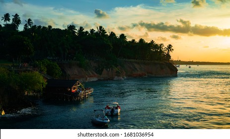 Beautiful cliff coastline in Tibau do Sul during a bright summer sunset with a large river and boats in the background