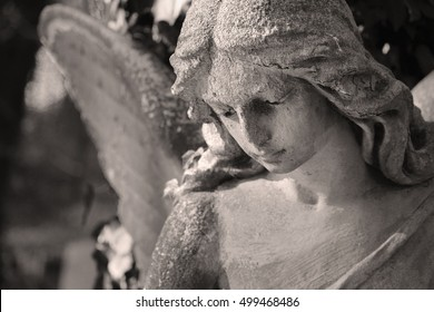 Beautiful close up af a face angel marble sculpture with a sweet expression that looks down (Black and White)