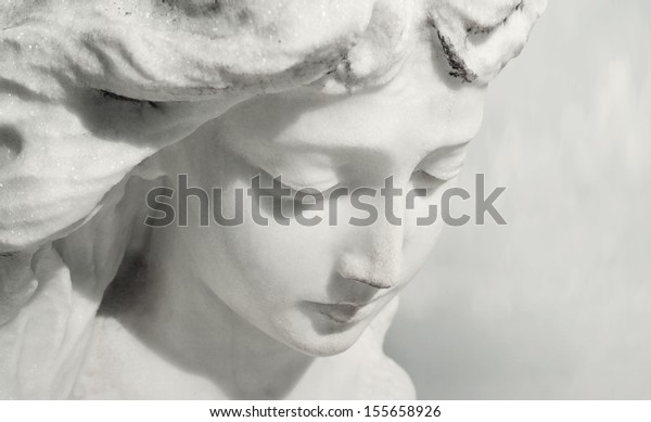 Beautiful close up af a face angel marble sculpture with a sweet expression that looks down