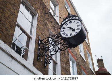 Beautiful close up of a big black clock on Doughty Street, Holborn district, London Borough of Camden (England, United Kingdom). Low-angle shot. Brick house near Charles Dickens. English architecture.
