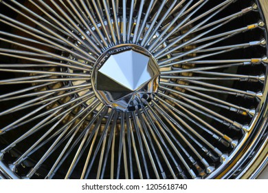 A beautiful close up image of an intricately designed spoked hubcap.