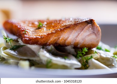 Beautiful close up of a roasted salmon stake on pasta plate. Macro food. Fresh salmon pasta. Fried salmon fish on pasta. Mediterranean dish. white plate. fine dining. Beautiful food. Farfalle