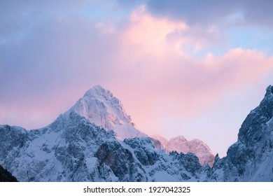 Beautiful close up shot of a pink glowing Mountain top in the Alps at sunset while wind is blowing snow off the Mountain into pink and purple clouds. Power of natural elements in an alpine surrounding