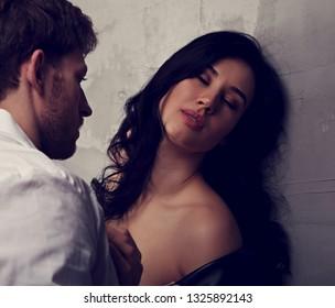 Beautiful closed eyes enjoying woman hugging her husband with deeping thinking eyes. Closeup art drama emotional portrait. Toned