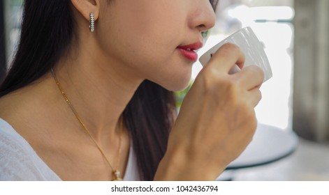Beautiful closeup of Asian woman drinking coffee. (Selected focus)