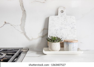 A beautiful closeup of a custom designed kitchen, with marble looking quartz countertop and backsplash. Decorated by marble cheese board and little indoor planter.