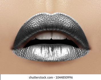 Beautiful closeup with female plump lips with silver color makeup. Christmas celebrate make-up, glitter sparkles on lip. Shine christmas style. Metalic makeup