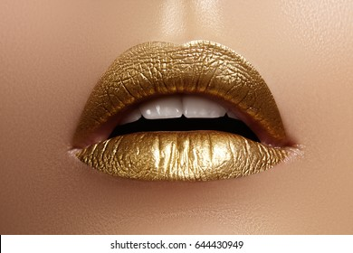Beautiful closeup with female plump lips with gold color makeup. Fashion celebrate make-up, glitter cosmetic. Shine christmas style. Metalic makeup