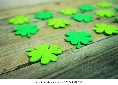 Beautiful close-up of many irish shamrocks, feast clovers, in a row that remind luck or Saint Patrick's Day with bokeh and wooden tables as background