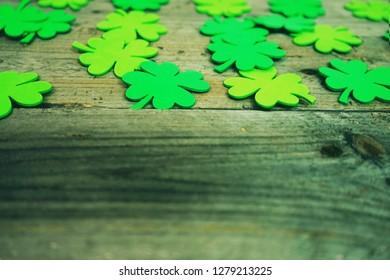 Beautiful close-up of many irish shamrocks, feast clovers, in a row that remind luck or Saint Patrick's Day and wooden tables as background