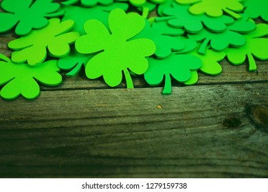 Beautiful close-up of a pile of green shamrocks or feast clovers over wooden tables that remind Saint Patrick's Day or lucky with space