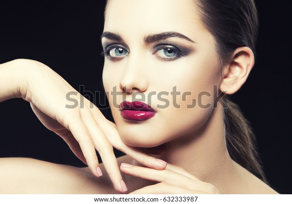 Beautiful close-up portrait of fashion woman model with glamour bright makeup, dark magenta lipstick. Evening catwalk visage, trend style