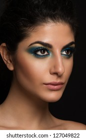 Beautiful closeup portrait of young caucasian female on black background. Dark blue and yellow makeup, natural lips, perfect skin. Big brown eyes with long eyelashes.