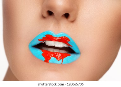 Beautiful closeup portrait of young caucasian female on white background. Light blue lips with red accent makeup, perfect skin.