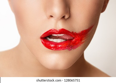 Beautiful closeup portrait of young caucasian female,red smeared lips, white teeth