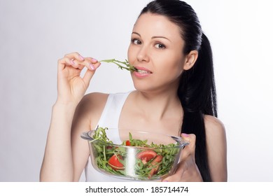 Beautiful close-up portrait of young woman eating salad. Healthy food concept. Skin care and beauty. Vitamins and minerals.