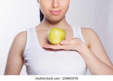 Beautiful close-up portrait of young woman with green apple. Healthy food concept. Skin care and beauty. Vitamins and minerals.