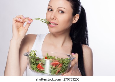 Beautiful close-up portrait of young woman eating salad and vegetables. Healthy food concept. Skin care and beauty. Vitamins and minerals.