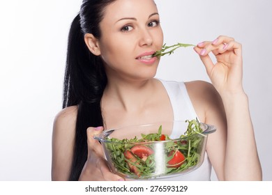 Beautiful close-up portrait of young woman eating salad and vegetables isolated on white background. Healthy food concept. Skin care and beauty. Vitamins and minerals.