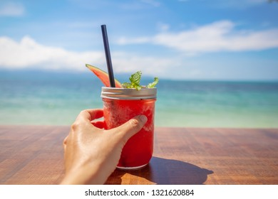Beautiful closeup of red watermelon shake  on the table  on tropical sea background. Detox day.