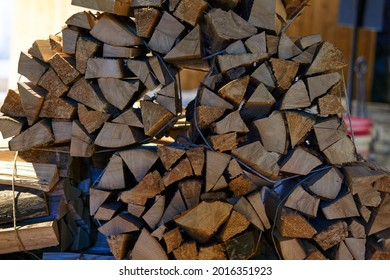 A beautiful closeup view of cut and split firewood stacked outdoor up against a shed under roof . High quality photo