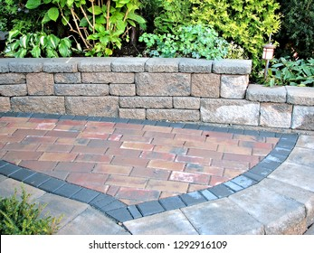 A beautiful closeup view footpath with step backed by block retaining wall and paver walkway part of garden landscape design