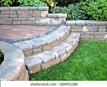 A beautiful closeup view of rounded two step staircase design off green lawn grass built with concrete blocks and incorporated low retaining wall
