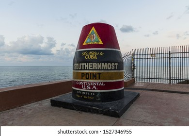 Beautiful closeup view of Southernmost Point Buoy on blue water of Atlantic OCean and blue sky background. Tourist attraction. Key West, Florida. USA. 09.07.2019.