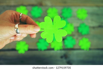 Beautiful close-up of woman hand holds a green irish shamrock with a pile of feast clovers over wooden tables as background bokeh that remind luck