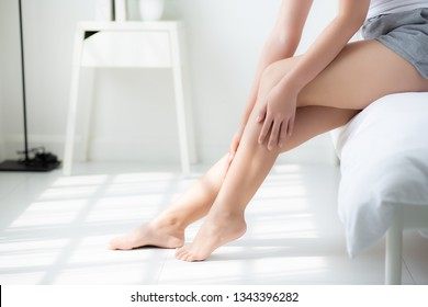 Beautiful closeup young asian woman sitting on a bed stroking legs with soft smooth skin in the bedroom, girl applying body cream and lotion with treatment, healthy and wellness concept.