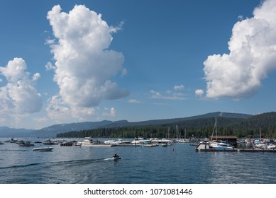 Beautiful clouds hang over the harbor area near Tahoe City, as boaters enjoy the warm summer weather and calm waters on Lake Tahoe.