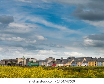 Beautiful clouds over Galway city, yellow flowers in foreground, South park, the Claddagh, Warm sunny day, Rich colors.