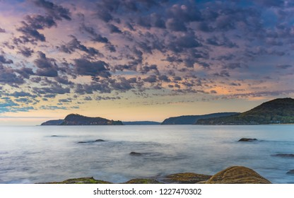 Beautiful Clouds over a Gentle Sea at Sunrise - Pearl Beach on the Central Coast, NSW, Australia.