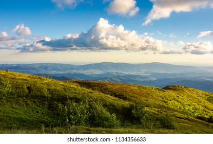 beautiful clouds over the summer mountain landscape. grassy hills and distant mountains in evening side light. gorgeous colorful scenery with interesting shapes and perspective