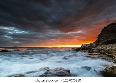 Beautiful clouds at sunset on the rocky seashore