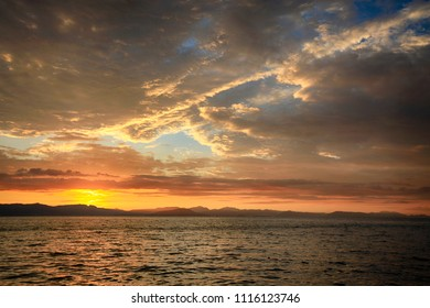 Beautiful clouds at sunset in the sky over the sea off the coast of the island of Corfu in Greece