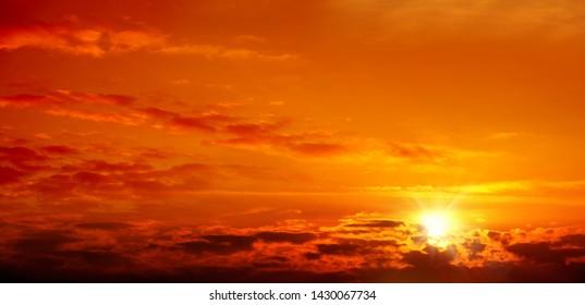 Beautiful cloudscape of orange colored sunset sky with shining sun