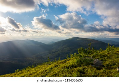 beautiful cloudscape over the summer mountains. grassy hills and distant mountains in evening side light. gorgeous colorful scenery with interesting shapes and perspective