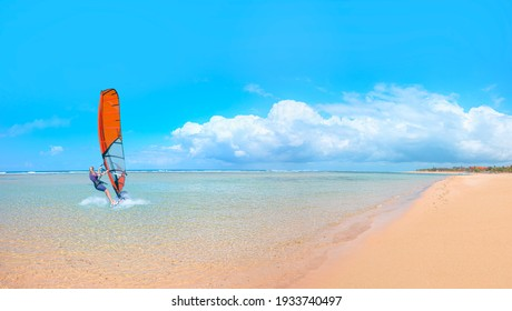 Beautiful cloudy sky with Windsurfer Surfing The Wind On Waves - Panoramic seaview with picturesque beach at sunset - Bali, Indonesia