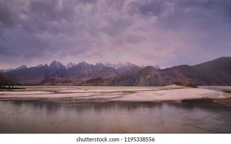 Beautiful cloudy sunset hour in mountains of Shiachen which are reflected in Shyok river.   Skardu Pakistan