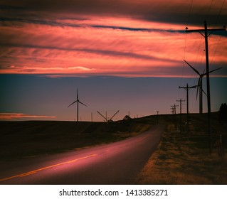 A beautiful cloudy sunset reflects on a country road surrounded by farm fields and wind turbines in rural Idaho.