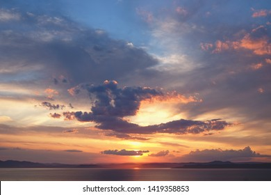 Beautiful cloudy sunset and sea landscape. Pink and gold colored sky in the evening.