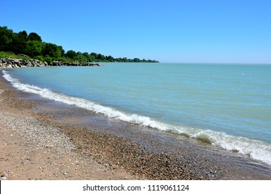 Beautiful coast line beach with a wave ripple along the entire shoreline on a sunny day.