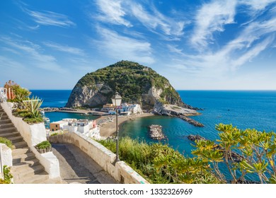 Beautiful coast of small village Sant'Angelo, giant green rock in blue sea near Ischia Island, Italy. Sunny day, blue sky with white clouds and azure sea.