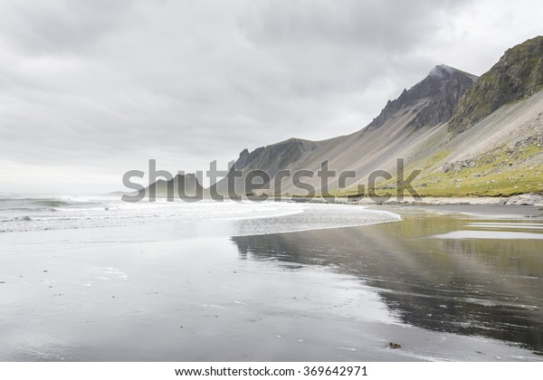 Beautiful coast Stokksnes with view to Atlantic ocean and mountains. Reflection in the water. East of Iceland.