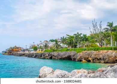 Beautiful coastal cliffside turquoise ocean on Caribbean island. Sunny summer vacation day on the coast of Montego Bay, Jamaica. Ideal tropical tourist destination. Margaritaville in background.