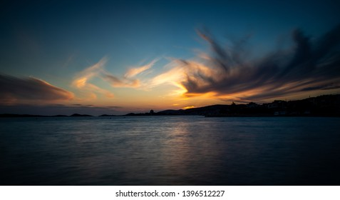 Beautiful coastal sunset with blurred sunset clouds.