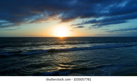A beautiful coastal sunset over gentle rolling waves in north county San Diego Southern California west coast Pacific Ocean and clouds