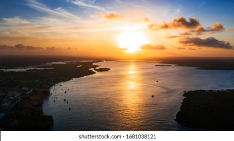 Beautiful coastline in Tibau do Sul during a bright summer sunset with a large river and boats in the background